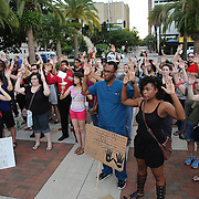 """People raise their arms in Lake Eola park during the """"National Moment of Silence"""" event at the Lake Eola bandshell in downtown Orlando, Florida on Thursday, August 14, 2014. In light of the recent killing of eighteen year old Mike Brown in Ferguson, Missouri, citizens across America are gathering in solidarity to hold vigils and observe a moment of silence to honor victims of suspected police brutality. (AP Photo/Alex Menendez)"""