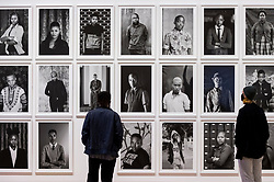 """© Licensed to London News Pictures. 03/11/2020. LONDON, UK. Staff members view works from the ongoing series """"Faces and Phases"""". Preview of the first major UK exhibition by South African visual activist Zanele Muholi at Tate Modern.  260 photographs document black lesbian, gay, trans, queer and intersex lives in South Africa.  The show runs 5 November to 7 March 2021, but will be interrupted by England's coronavirus pandemic lockdown currently due to last 5 November to 2 December.    Photo credit: Stephen Chung/LNP"""