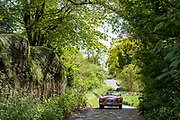 Man driving open top convertible MG sports car in The Cotswolds, UK