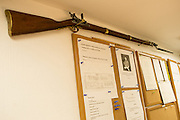 New York, NY, - December 8, 2013. A musket hangs above a bulleltin board opposite the kitchen pass-through. Along with a plan of the dining room and work-related postings Lambert posts quotations and aphorisms relating to food, work and life.