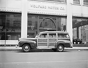 """Ackroyd 00078-50. Western Skyways. March 21, 1947. Station wagon."""" Parked in front of Wolfard Motor Co., 1207 West Burnside. Across the street from the Crystal Hotel. Mecca Hotel sign."""