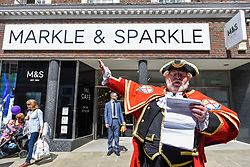 "© Licensed to London News Pictures. 18/05/2018. LONDON, UK.  A town crier gives a speech outside the temporarily renamed ""Markle and Sparkle"" (usually Marks and Spencer) store in Windsor for the wedding between Prince Harry and Meghan Markle on 19 May continue.  Tens of thousands of people are expected to visit the town for what has been billed as the wedding of the year. Photo credit: Stephen Chung/LNP"