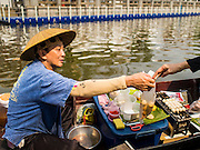 12 FEBRUARY 2015 - BANGKOK, THAILAND:  A vendor in a canoe sells grilled meat to customers at a new floating market opened in Khlong Phadung Krung Kasem, a 5.5 kilometre long canal dug as a moat around Bangkok in the 1850s. The floating market opened at the north end of the canal near Government House, which is the office of the Prime Minister. The floating market was the idea of Thai Prime Minister General Prayuth Chan-ocha. The market will be open until March 1.    PHOTO BY JACK KURTZ