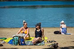 © Licensed to London News Pictures. 14/06/2021. LONDON, UK.  People sunbathe on the beach at Ruislip Lido in north west London.   The forecast is for the temperature to rise to 28C, the hottest day of the year so far.  Photo credit: Stephen Chung/LNP