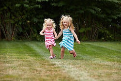 Two Young Girls Running in Garden Holding Hands