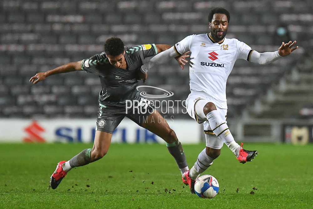 Fleetwood Town forward James Hill (33) battles for possession  with Milton Keynes Dons forward Cameron Jerome (35) during the EFL Sky Bet League 1 match between Milton Keynes Dons and Fleetwood Town at stadium:mk, Milton Keynes, England on 19 January 2021.