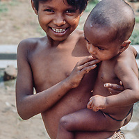 Homeless and malnourished village children from Bangladesh find a moment to smile at Mirpur Destitute Camp near Dhaka, Bangladesh. in 1977.  Their mother had been left widowed, violated and destitute after both a cyclone and subsequent war of indepence in 1971.