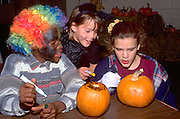 Friends age 11 painting pumpkins at Youth Express Halloween party.  St Paul  Minnesota USA