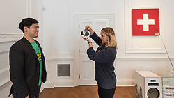"© Licensed to London News Pictures. 05/10/2018. LONDON, UK. A visitor has a passport photo taken by the artist's assistant. Preview of ""Swiss Passport Office"" by American artist Tom Sachs at Galerie Thaddaeus Ropac in Mayfair.  To coincide with Frieze Week, the gallery will remain open for 24 hours from 6pm 5 October to 6pm 7 October for the issuing of serial-numbered Tom Sachs Swiss passports for visitors.  The installation reflects the concerns relating to Brexit, Syria and Donald Trump's immigration policies and challenges the notion of global citizenship.  Photo credit: Stephen Chung/LNP"