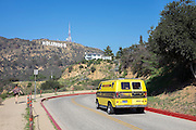 © Licensed to London News Pictures. 15/02/2015. Los Angeles, USA . A yellow van follows a road up near the Hollywood sign. Tourists photograph the Hollywood sign in Los Angeles, California. Photo credit : Stephen Simpson/LNP