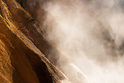 The Grand Canyon of Yellowstone is filled with mist from Lower Yellowstone Falls, backlit by the morning sun.