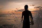 A surfer is silhouetted against a sunset and splashing water on the Kapahulu Groin