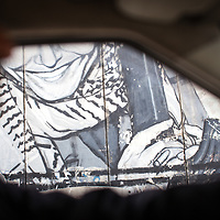A fragment of a mural seen through the window of a moving car in Bethlehem. The Israeli West Bank barrier or wall is a separation barrier in the West Bank. Israel calls it a security barrier while Palestinians and many others call it a racial segregation or apartheid wall. At a total length of 708 kilometres (440 miles) upon completion, the border traced by the barrier is more than double the length of the Green Line, with 15% running along it or in Israel, while the remaining 85% cuts at times 18 kilometres (11 miles) deep into the West Bank, isolating about 9.4% of it, leaving an estimated 25,000 Palestinians isolated from the bulk of that territory.