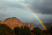 A vibrant rainbow arcs over the Twin Buttes, a sandstone formation near Sedona, Arizona.