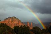 A vibrant rainbow arcs over the Twin Buttes, a sandstone formation near Sedona, Arizona.