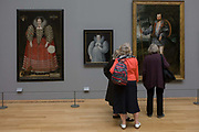 Three women admire Tudor portraits of Elizabethan nobility in Tate Britain, London. On the left is a portrait of Mary Kytson, of Lady Darcy of Chiche, later, Lady Rivers, British School, circa 1590. In the middle is a painting attributed to Marcus Gheeraerts II of an Unknown Lady circa 1595. The three ladies however are admiring the picture of Captain Thomas Lee, also by Gheeraerts II, 1594. Tate first opened its doors to the public in 1897 with one site, displaying a small collection of British artworks. Today Tate has four major sites and the national collection of British art from 1500 to the present day and international modern and contemporary art, which includes nearly 70,000 artworks.