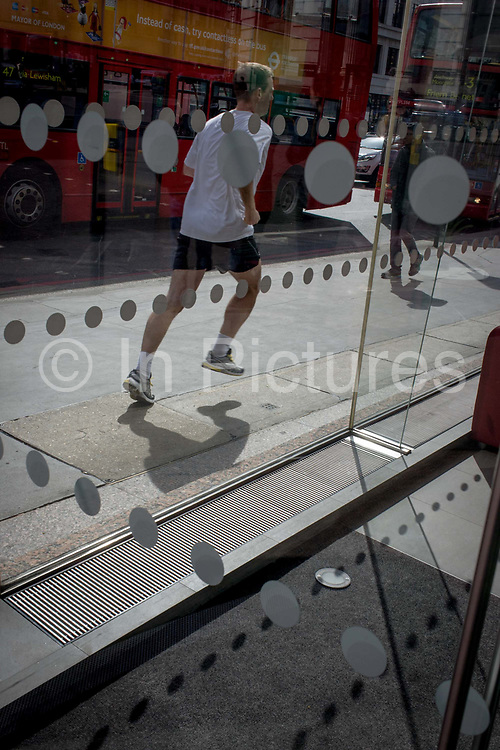 A jogger runs past an office foyer entrance featuring dots and circles (and shadows) on exterior windows in the City of London. The man is about to head south over London Bridge and passes these offices whose window theme is a series of dots, currently popular in the City of London - the capital's oldest financial district.