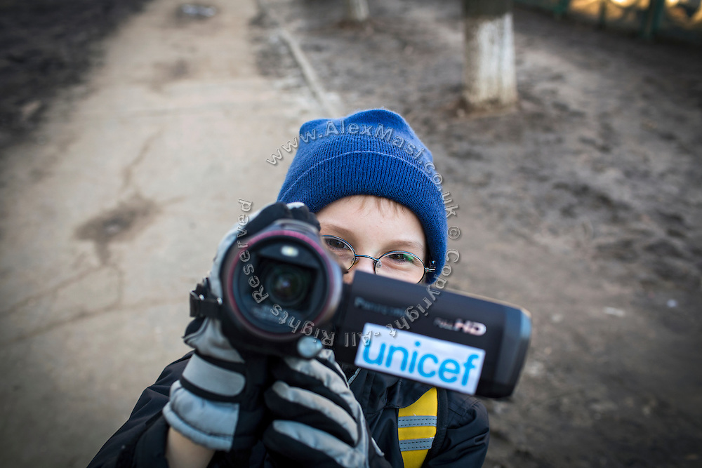 Yaroslav, 10, is using a UNICEF video camera near the provisional home where he resides with his mother Olga, 36, as internally displaced persons. (IDPs) Yeroslav is taking part to the UNICEF-sponsored One Minute Junior project for internally displaced persons (IDPs), carried out by the local NGO 'Ukrainian Frontiers' in the city of Kharkiv, the country's second-largest, in the east. The conflict between Ukrainian army and Russia-backed separatists nearby, in the Donbass region, have left more than 10000 dead since April 2014, including over 1000 since the shaky Minsk II ceasefire came into effect in February 2015. The approximate number of people displaced by the conflict is 1.4 million as of August 2015. Yeroslav's mother, Olga, is also a participant to a different project of 'Ukrainian Frontiers', called 'Self-Employment', first as a beneficiary, and now as a paid hotline coordinator for people seeking jobs and formation courses.