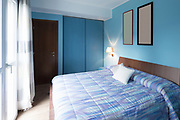 Blue bedroom with frames on the wall. Nobody inside