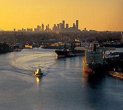 Tugboat and shipping vessels in the ship channel at the Port of Houston with the downtown Houston skyline on the horizon at sunset.