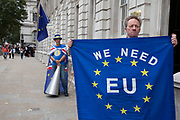 Anti Brexit protester with a European Union flag reading We need EU outside the Cabinet Office in Westminster as inside the Tory Cabinet meets to discuss Brexit on 16th August 2019 in London, England, United Kingdom.