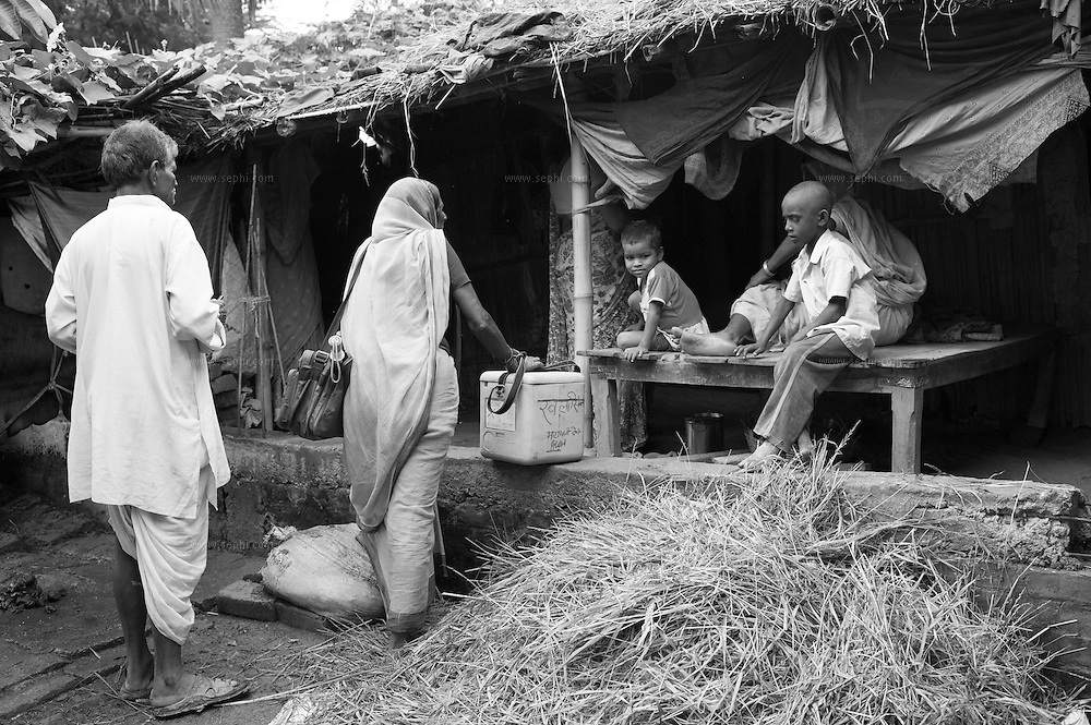 A vaccinator team at the entrance to a village home during vaccination day at a village on the flood plains of the Kosi river near Kusheshwar Asthan (E), Bihar.