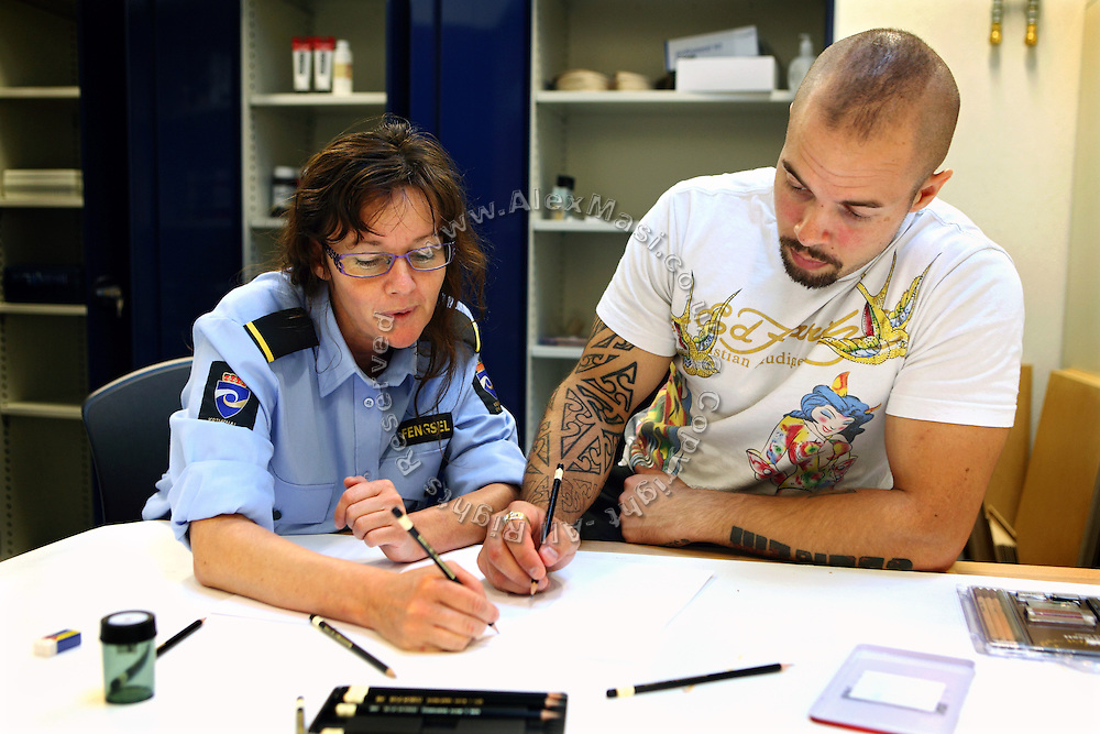 An inmate (right) is practicing drawing along a woman guard during an art lesson at the school inside the premises of the luxurious Halden Fengsel, (prison) near Oslo, Norway.