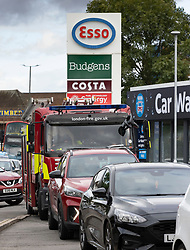 © Licensed to London News Pictures. 05/10/2021. London, UK.  A long queue of vehicles, including a fire engine, line up to buy fuel at an ESSO petrol station in New Malden, south London. Military personnel have started helping with driver shortages following more than a week of long queues and closures at petrol stations. Photo credit: Peter Macdiarmid/LNP