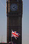 A Union Jack flag and in the background, the Elizabeth Tower of the British parliament, on 17th January 2017, in London England. The Elizabeth Tower (previously called the Clock Tower) named in tribute to Queen Elizabeth II in her Diamond Jubilee year – was raised as a part of Charles Barry's design for a new palace, after the old Palace of Westminster was largely destroyed by fire on the night of 16 October 1834. The new Parliament was built in a Neo-gothic style. Although Barry was the chief architect of the Palace, he turned to Augustus Pugin for the design of the clock tower. It celebrated its 150th anniversary on 31 May 2009. The tower was completed in 1858 and has become one of the most prominent symbols of both London and England.