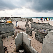 """""""We were once three miles from the sea.""""<br /> <br /> The fishing village of Totope, near Ada, Ghana, pictured on 9 March 2010, is disappearing as the encroaching sea and worsening coastal erosion bury villagers' homes in sand. Trapped between the sea and a lagoon, the village has nowhere to go."""