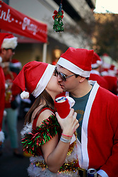 13 December 2014. New Orleans, Louisiana. <br /> Samantha Gould and David Burford kiss at the 4th annual running of the Santas in downtown New Orleans. Proceeds from the event benefit 'That Others May Love' charity.<br /> Photo; Charlie Varley/varleypix.com