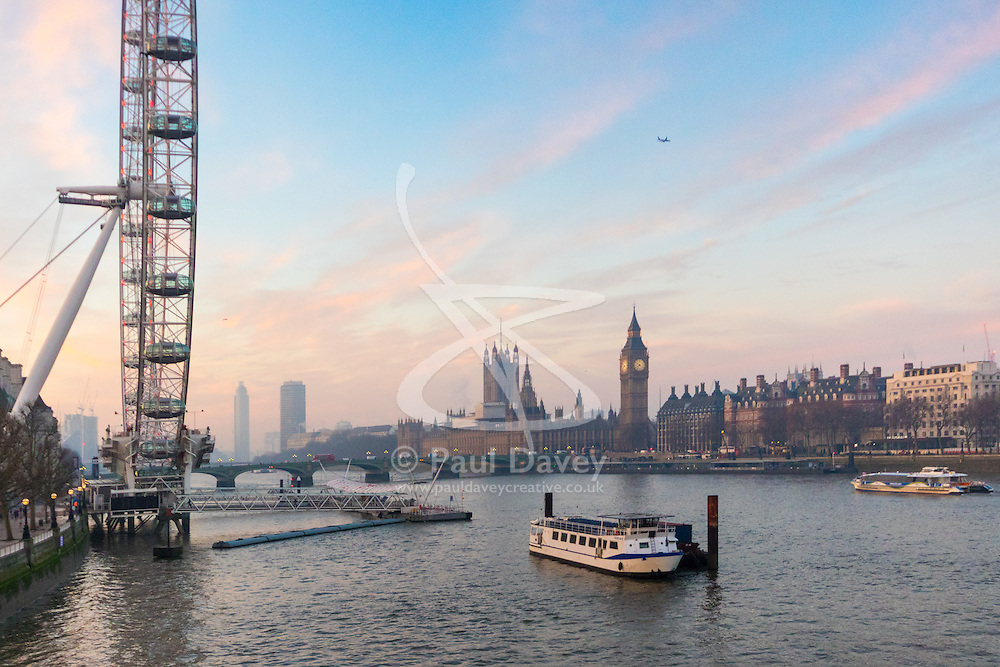 London, January 24th 2017. Photographed from Hungerford Bridge, the early morning light illuminates clouds and buildings of the city's skyline, with the predicted fog failing to appear. High pressure over the UK has caused pollution alerts as fumes are trapped beneath a cold layer of air.  PICTURED: The early morning sky creates a soft, pastel-toned backdrop for the Houses of Parliament.