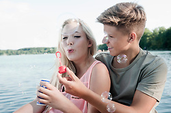 Teenage couple blowing soap bubbles on a jetty at lake