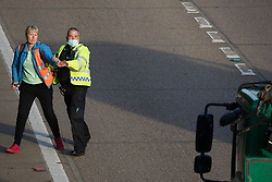 Ockham, UK. 21st September, 2021. An Insulate Britain climate activist tries to walk into the clockwise carriageway of the M25 between Junctions 9 and 10 as part of a campaign intended to push the UK government to make significant legislative change to start lowering emissions. Both carriageways were briefly blocked before being cleared by Surrey Police. The activists are demanding that the government immediately promises both to fully fund and ensure the insulation of all social housing in Britain by 2025 and to produce within four months a legally binding national plan to fully fund and ensure the full low-energy and low-carbon whole-house retrofit, with no externalised costs, of all homes in Britain by 2030.