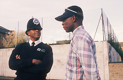 Community police officer standing in street talking to teenage boy,
