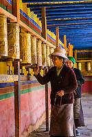 A Tibetan pilgrim turns prayer wheels as she circumambulates around the Tandruk Monastery, Tibet (Xizang), China