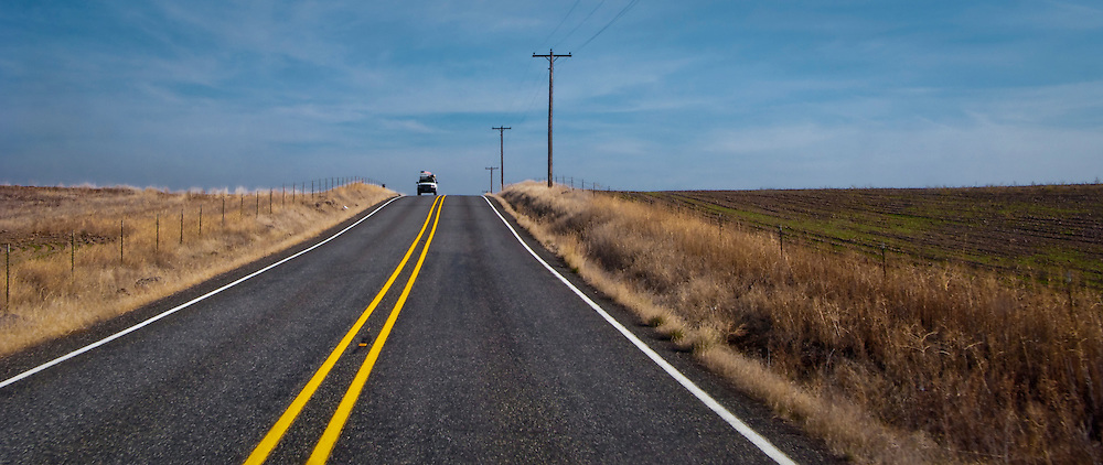 A loaded vehicle comes into view over a crest in the road in rural Klickitat County, WA, USA