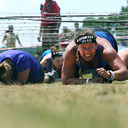 Amy Guandalini in action at the barbed wire crawl obstacle during the Reebok Spartan Race. Mohegan Sun, Uncasville, Connecticut, USA. 28th June 2014. Photo Tim Clayton