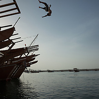 Boys leap from dhows, traditional sailing, fishing or trading boats, in a delight of acrobatics at a port in Sur, an area famous for wooden boat building on the Gulf of Oman.