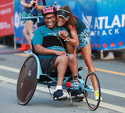 July 4, 2018 - Atlanta, GA, USA - Curtis Ward gets a hug from Yvonne Leeb after finishing the push assist race during the AJC Peachtree Road Race on Wednesday, July 4, 2018, in Atlanta. (Credit Image: © Curtis Compton/TNS via ZUMA Wire)