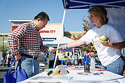 Rensheng Sun, left, of San Jose talks with Betty Reutter of the Emergency Preparedness Commission about Milpitas' free emergency preparedness classes during the Milpitas Executive Lions Club's Make A Difference Day at Seasons Marketplace in Milpitas, California, on October 16, 2013. (Stan Olszewski/SOSKIphoto)