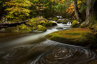 A long exposure creates a swirling pattern in the surface of a small stream in Groton State Forest, VT.
