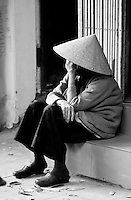 A woman wearing a conical hat sits on a step contemplating.