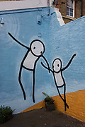Mural by the artist known as Stik, painted on a wall at Push Studios, Blackwater Street, East Dulwich. Stik people, although androgenous and constructed from simple shapes, are nevertheless capable of conveying complex body language and emotion. These themes of human emotion and expression are infused in Stik's brightly coloured street art. Stik, the street artist, himself was homeless for a period and ideas surrounding human vulnerability are also detectable in his art. Stik has been creating Stik people around London for over ten years