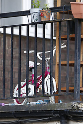 © Licensed to London News Pictures. 01/07/2020. London, UK. A child's bicycle remains outside a block of flats in Monarch Parade in Mitcham, south London after a four year old girl was found seriously injured yesterday. She was taken to hospital where she later died. A woman, aged 35, is fighting for her life after she was also found suffering serious injuries inside the property. Photo credit: Peter Macdiarmid/LNP
