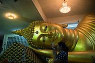A woman walks past a reclining Buddha statue at Wat Vorachanyawas Pier in Bangkok, Thailand. (November 2017)