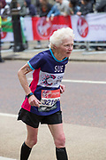 An elderly woman running for Cancer Research UK charity at Birdcage Walk during The Virgin London Marathon on 28th April 2019 in London in the United Kingdom. Now in it's 39th year, the London Marathon is a large sporting event with over 40,000 runners expected to take part.