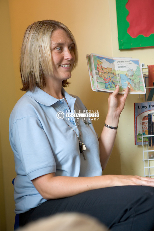 Nursery nurse reading a story to her class,