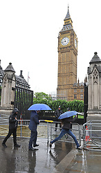 A person jumps over a puddle of rain water outside the Palace of Westminster in central London.