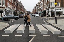 © Licensed to London News Pictures. 01/03/2019. London, UK.  Pedestrians walks across the UK's first 3D zebra crossing in St Johns Woord, North London in a bid to slow down the traffic.The optical illusion, which creates a floating effect, has been introduced in St John's Wood by Westminster City Council as part of a 12-month trial. Photo credit: Ray Tang/LNP